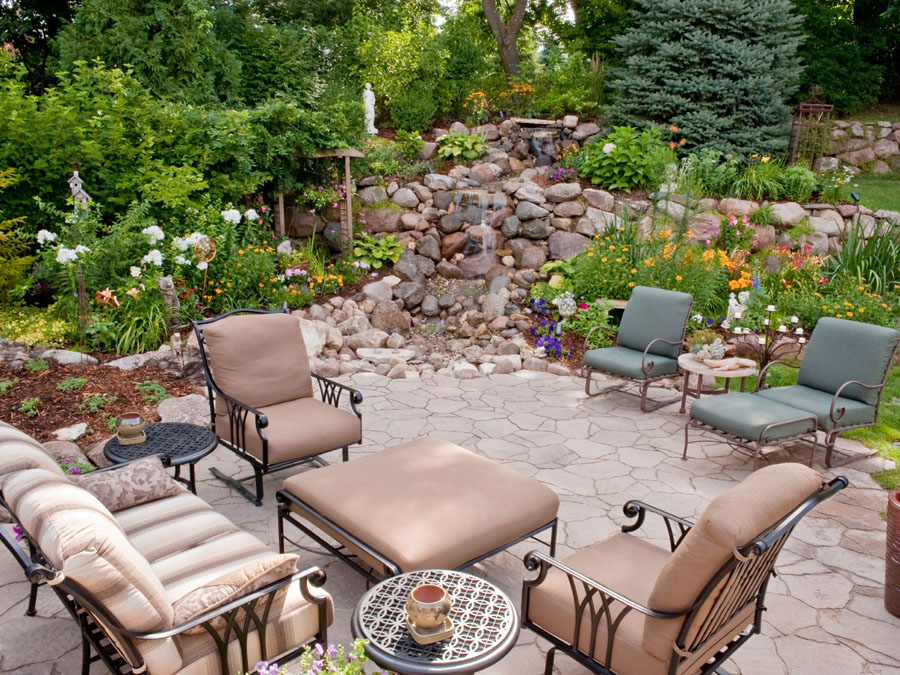 A garden patio with a pondless waterfall in the morning light.